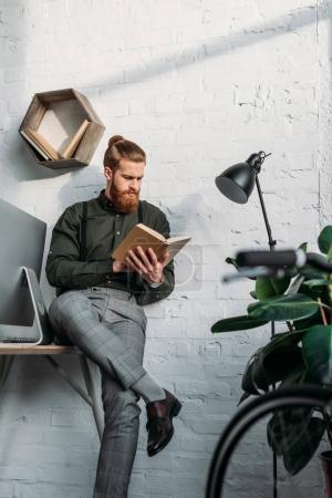 Photo pour Bel homme d'affaires assis sur la table et le livre de lecture - image libre de droit