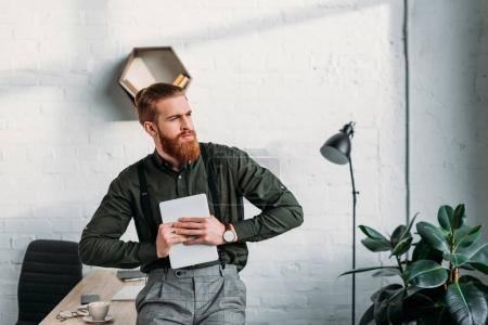 businessman holding tablet and looking away