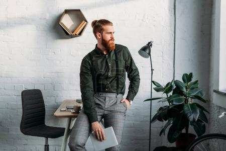 businessman leaning on table, holding tablet and looking away