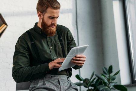 Photo pour Homme d'affaires grave avec tablette Bureau - image libre de droit