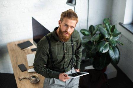 Photo pour Vue aérienne d'homme d'affaires tenant comprimé et en regardant la caméra - image libre de droit