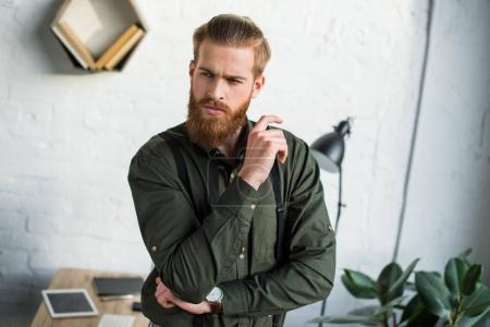 thoughtful bearded businessman looking away in office