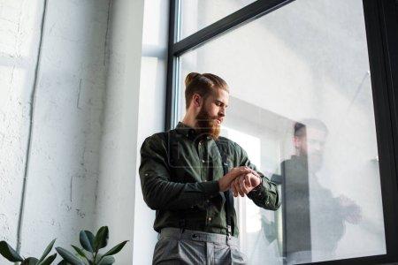 Photo pour Vue de dessous d'homme d'affaires contrôle de temps - image libre de droit