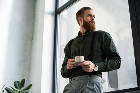 bottom view of businessman standing with cup of coffee and looking at window