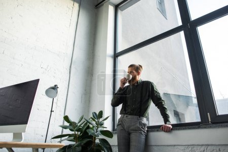bottom view of businessman drinking coffee in office