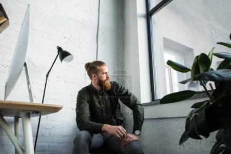 handsome bearded businessman sitting in office and looking away