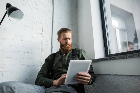 bearded businessman using tablet in office
