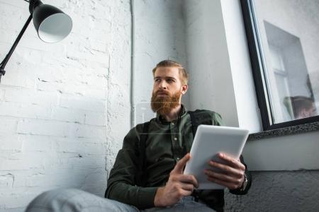 bearded businessman holding tablet and looking away