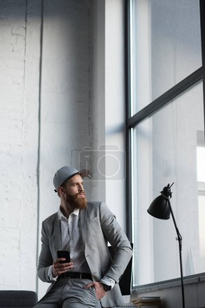 businessman in baseball cap holding smartphone and looking away