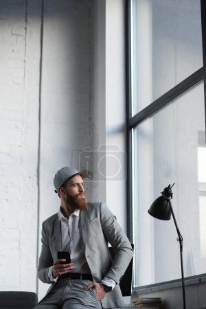 Photo pour Homme d'affaires dans la casquette de baseball maintenant smartphone et à la recherche de suite - image libre de droit