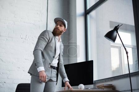 businessman in baseball cap looking away in office