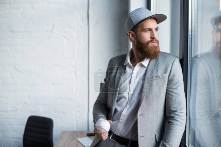 bearded businessman in baseball cap looking at window and holding baseball ball
