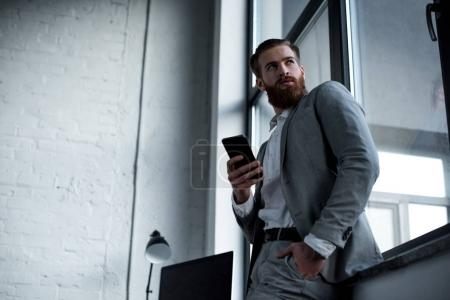 bottom view of handsome bearded businessman using smartphone in office and looking away