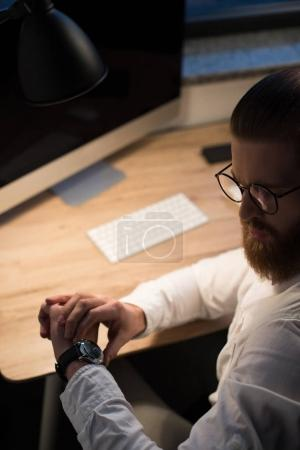 businessman looking at watch in office in evening