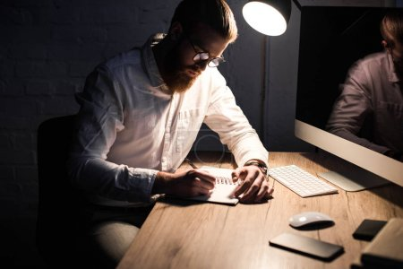 businessman writing something to notebook in office in evening