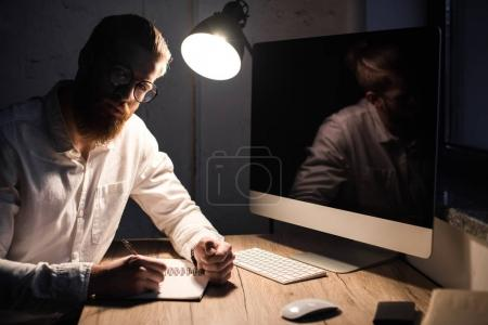businessman sitting with notebook in office and looking at camera