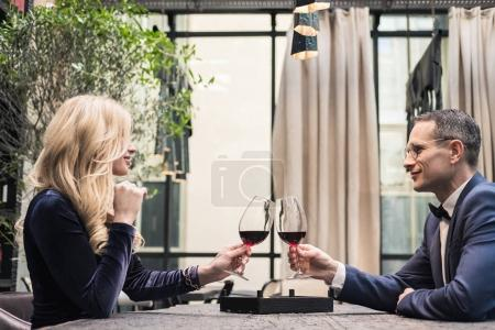 side view of happy adult couple clinking glasses of wine at restaurant