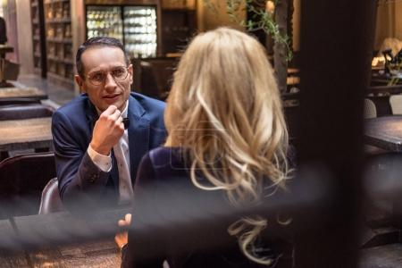 handsome adult man talking to his girlfriend at restaurant