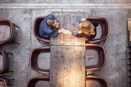 top view of adult couple holding hands on date at restaurant
