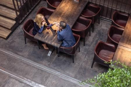 high angle view of adult couple holding hands on date at restaurant