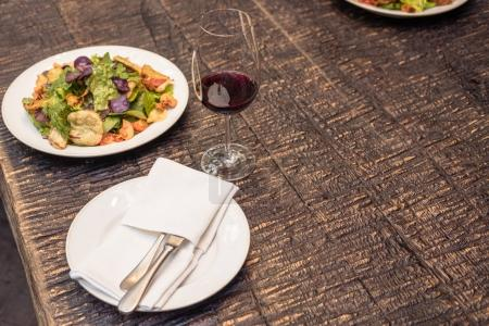 tasty salad with wine on rustic wooden table