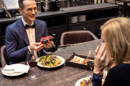 handsome adult man presenting valentines day gift to girlfriend at restaurant