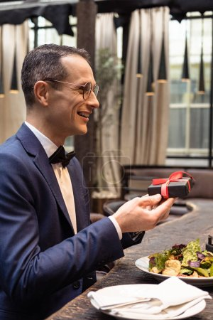 handsome man in stylish suit presenting valentines day gift at restaurant