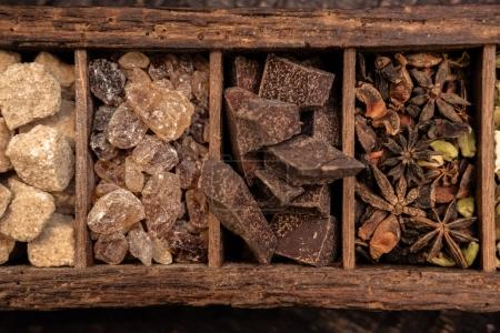 close-up shot of wooden box with various spices on table