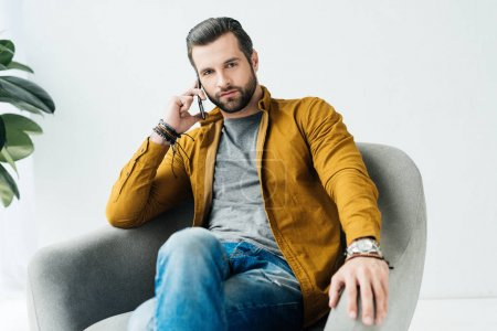 Photo for Handsome man talking by smartphone and looking at camera - Royalty Free Image