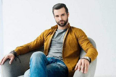 handsome man sitting in armchair and looking at camera