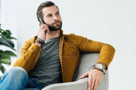 Photo for Handsome man talking by smartphone and looking up - Royalty Free Image