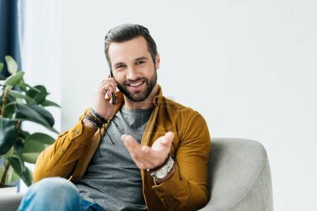 Photo for Handsome smiling man talking by smartphone and looking at camera - Royalty Free Image