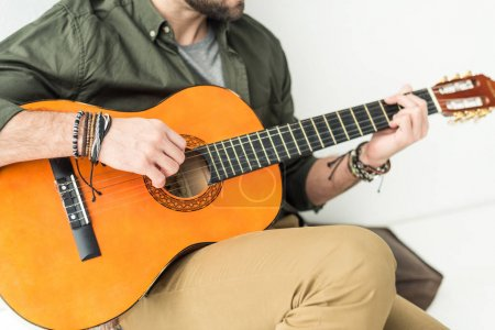 Photo for Cropped image of man sitting and playing acoustic guitar - Royalty Free Image