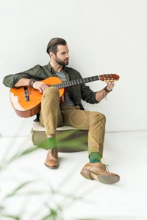 handsome man tuning acoustic guitar