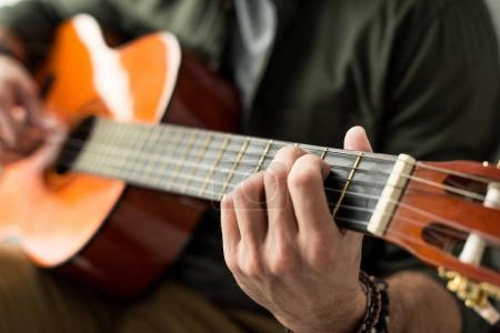 cropped image of man playing chord on acoustic guitar