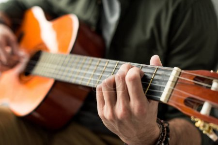 Photo for Cropped image of man playing chord on acoustic guitar - Royalty Free Image