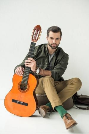 handsome man holding acoustic guitar and looking at camera on white