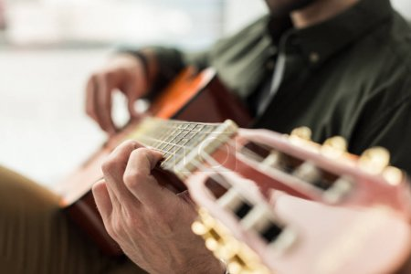 cropped image of musician playing acoustic guitar