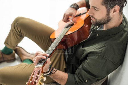 Photo pour Vue de la forte inclinaison du beau musicien jouant de la guitare acoustique - image libre de droit