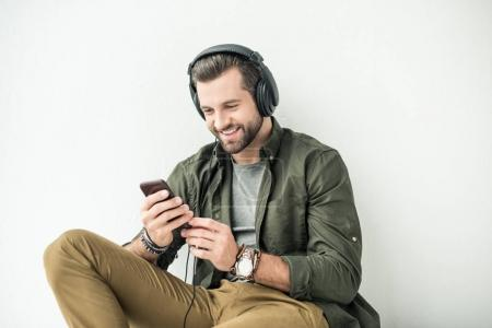 Photo for Handsome smiling man listening music with smartphone isolated on white - Royalty Free Image