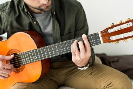 cropped image of man playing barre chord on acoustic guitar