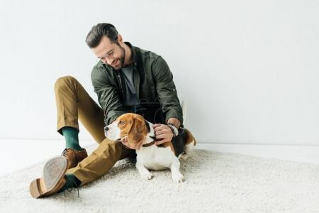 smiling handsome man playing with cute beagle on carpet