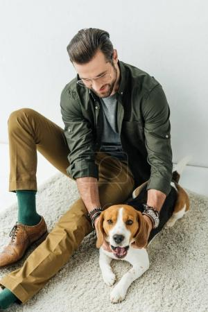 handsome man playing with yawning cute beagle on carpet