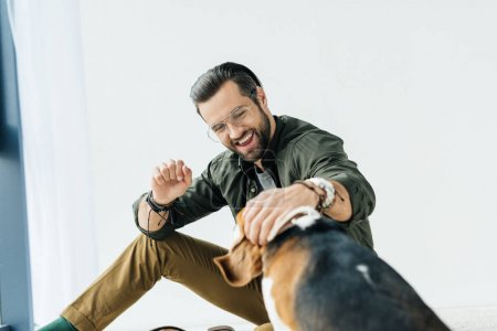happy man sitting on floor and playing with dog