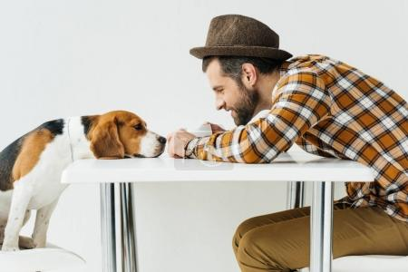 Photo for Side view of man touching dog nose at table - Royalty Free Image