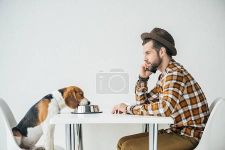 side view of man talking by smartphone at table with dog