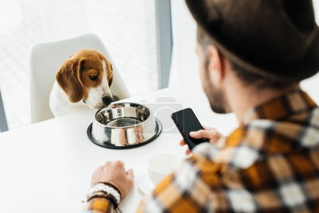 Photo for Man holding smartphone and looking at dog - Royalty Free Image