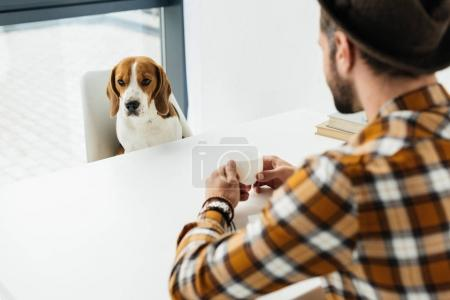 businessman sitting at table with coffee and looking at dog