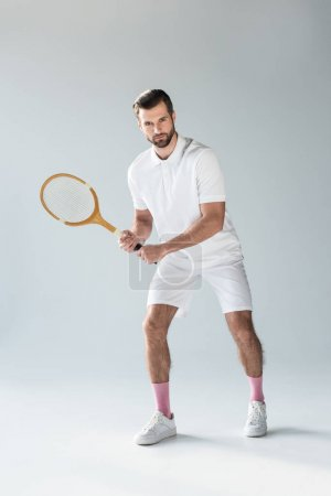 handsome tennis player with tennis racket looking at camera on grey