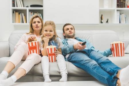 family with popcorn watching tv together at home